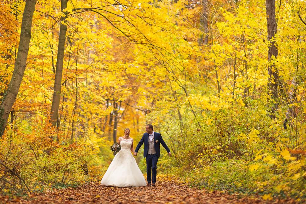 Brautpaar im Wald mit Brautstrauß im Herbst