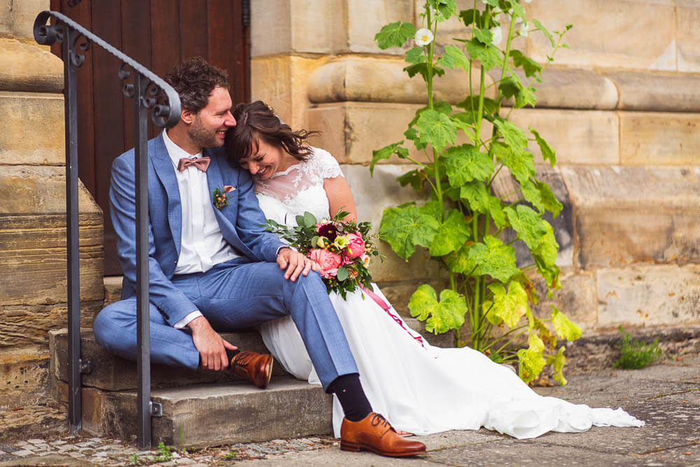 Brautpaar vor Kirche auf Treppe sitzend
